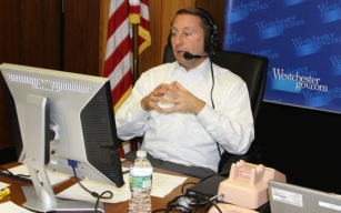 CE Astorino at the mike during a tele-town hall broadcast